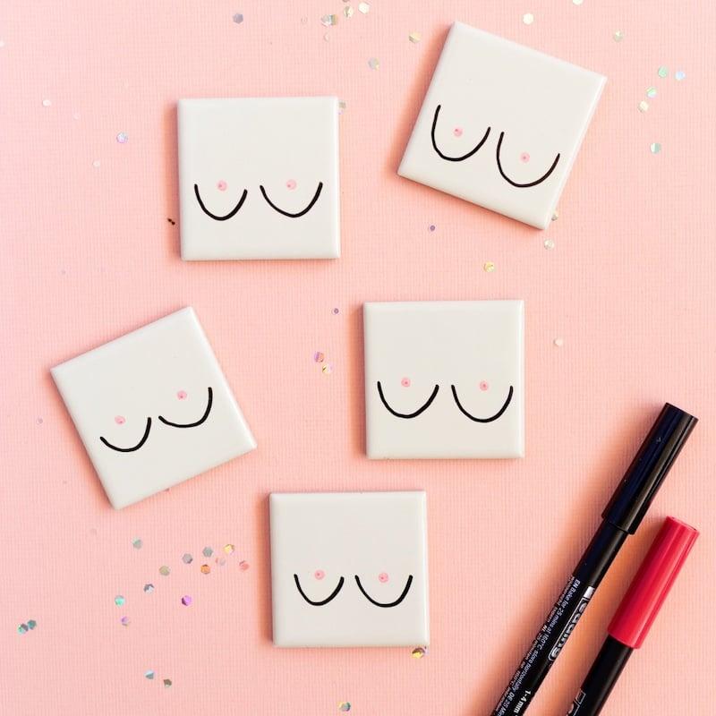 mini-tegeltjes-met-boobs-op-een-zalmroze-ondergrond-en-pennen-en-glitters-ernaast