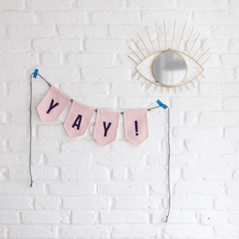 sfeerfoto-van-slinger-yay-in-het-roze-aan-bakstenen-muur-met-spiegel-ernaast